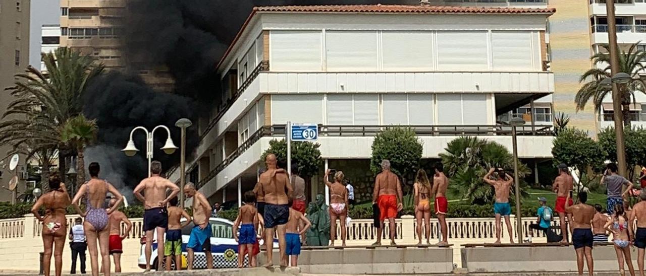 Los bañistas miran el humo provocado por el incendio de una furgoneta.