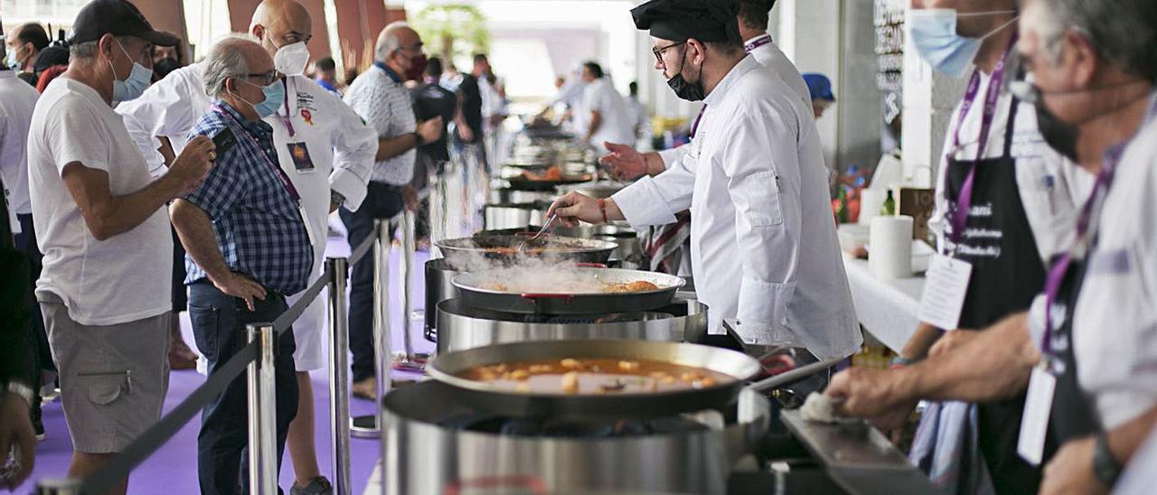 Un momento de la elaboración de las fideuaes por parte de los chefs inscritos y, a la derecha, el alcalde con el dueño y la cocinera del restaurante Casa Granero de Serra.                         ÀLEX OLTRA