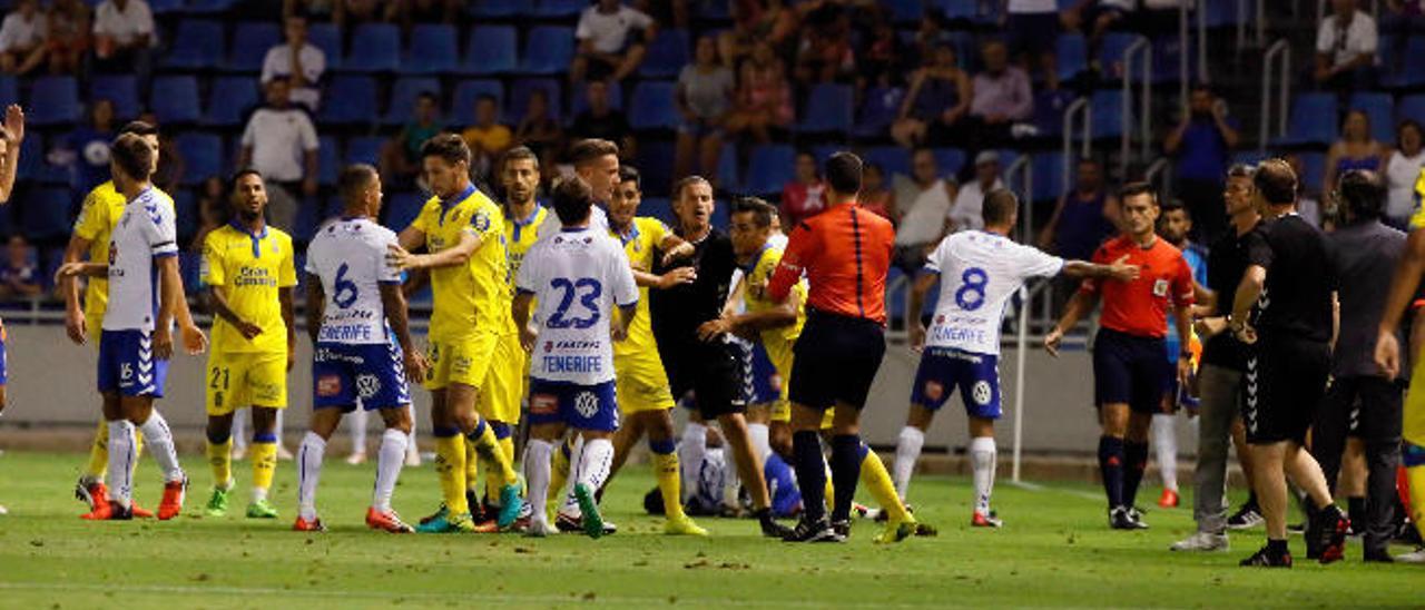 El lateral de la UD, David Simón, en el margen derecho, busca a Vitolo, dorsal 6, y que es agarrado por Arencibia, tras recibir un golpe por la espalda.