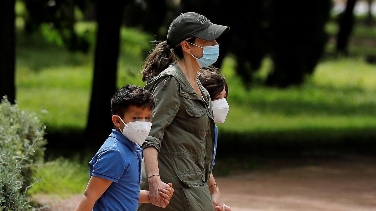 Una mujer pasea con dos niños en Valencia.