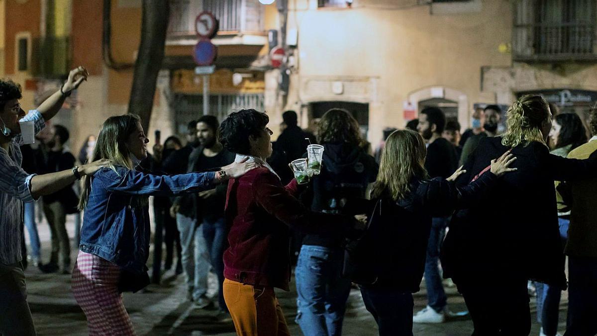 Varios jóvenes de fiesta en un botellón masivo en Barcelona, donde la policía desalojó a más de 7.000 personas la madrugada del sábado. | MARTA PÉREZ/EFE