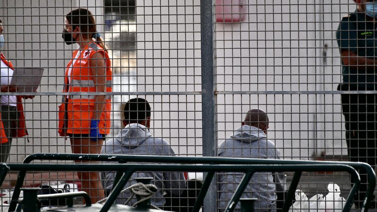 Migrantes son atendidos por la Guardia Civil y la Cruz Roja en Ceuta.