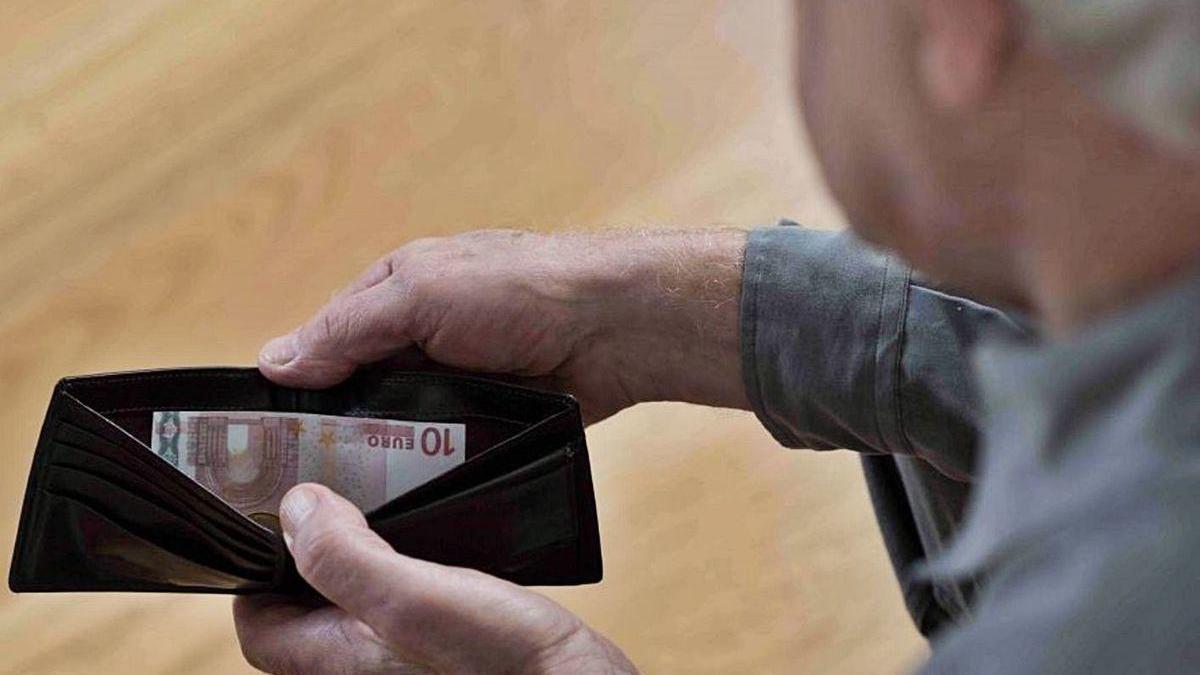 Un hombre saca dinero de su cartera.