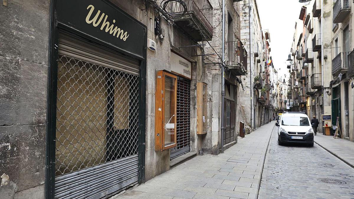 El carrer Ballesteries de Girona, amb les persianes abaixades d'alguns comerços