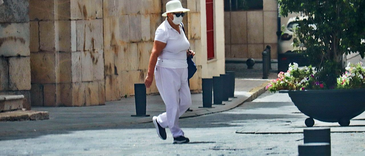 Una mujer camina protegida del sol con un gorro por Orihuela, uno de los municipios de la provincia en el que se registran las temperaturas más extremas. | TONYSEVILLA