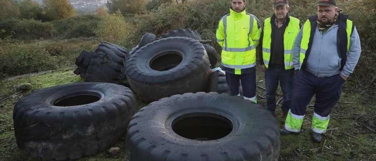 Tres operarios de la empresa contratada para retirar neumáticos del río Calvo, en A Cañiza. // Anxo Gutiérrez