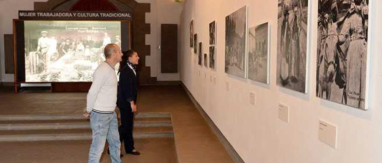 Dos personas observan varias de las fotos de la exposición en la ermita de San Pedro Mártir.