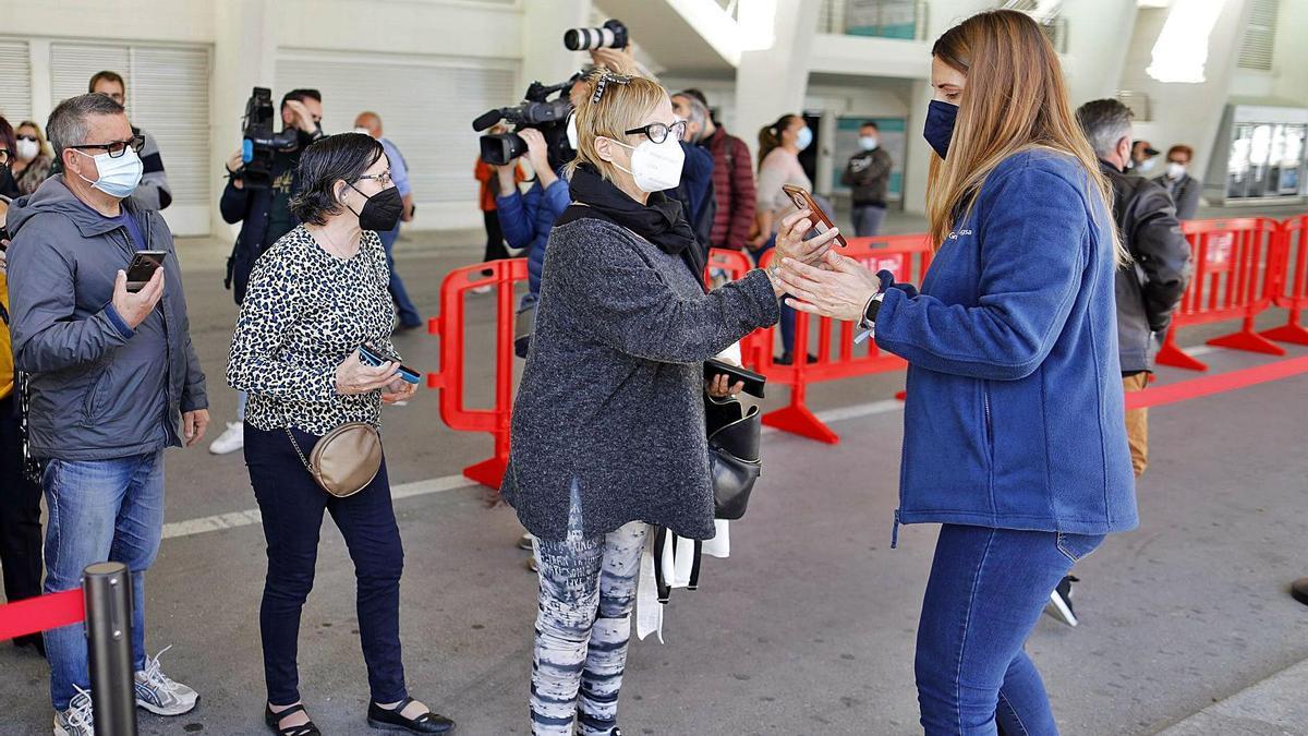 Una mujer muestra la citación de la vacuna en la pantalla de su móvil en la cola para inmunizarse en la Ciutat de les Arts i les Ciències.