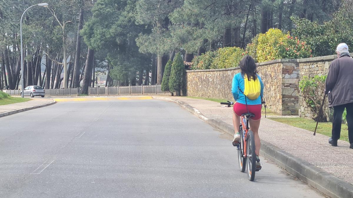 Una joven grovense en bicicleta y una persona mayor caminando por la isla.