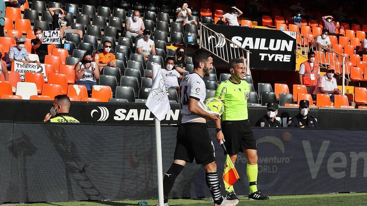 El capitán del Valencia CF, José Luis Gayá, transporta  el balón ante aficionados en la grada .  j.m.lópez