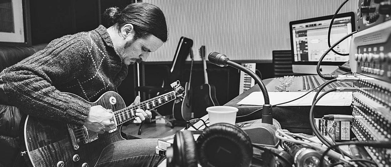 Joan Barbé toca la guitarra en su estudio, Magrana, de Santa Gertrudis./ Alejandro Iborra
