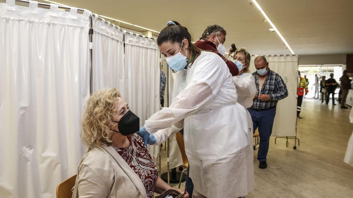 Una sanitaria inocula una dosis de Astrazeneca a una mujer en el Palacio de Congresos de Cáceres.