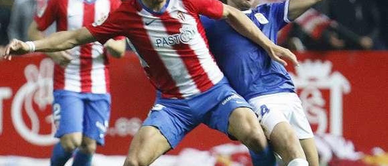 Álex Alegría protege la pelota ante Javi Muñoz.