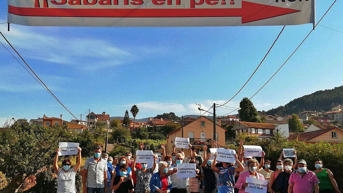 Decenas de vecinos de los barrios como Outeiro, Morade o Ribeira, concentrados ayer en el vial junto al en el que se prevé la estación de servicio bajo la pancarta.