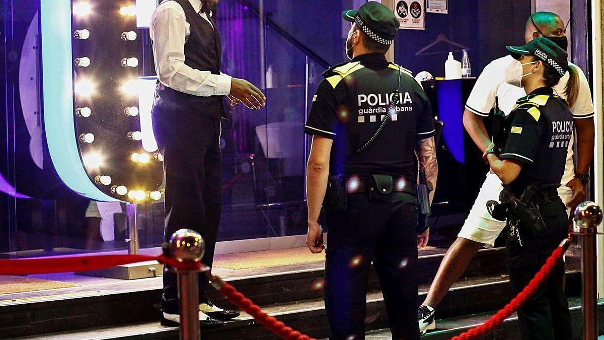 Una patrulla de la Guardia Urbana de Barcelona conversa con un trabajador de una discoteca.