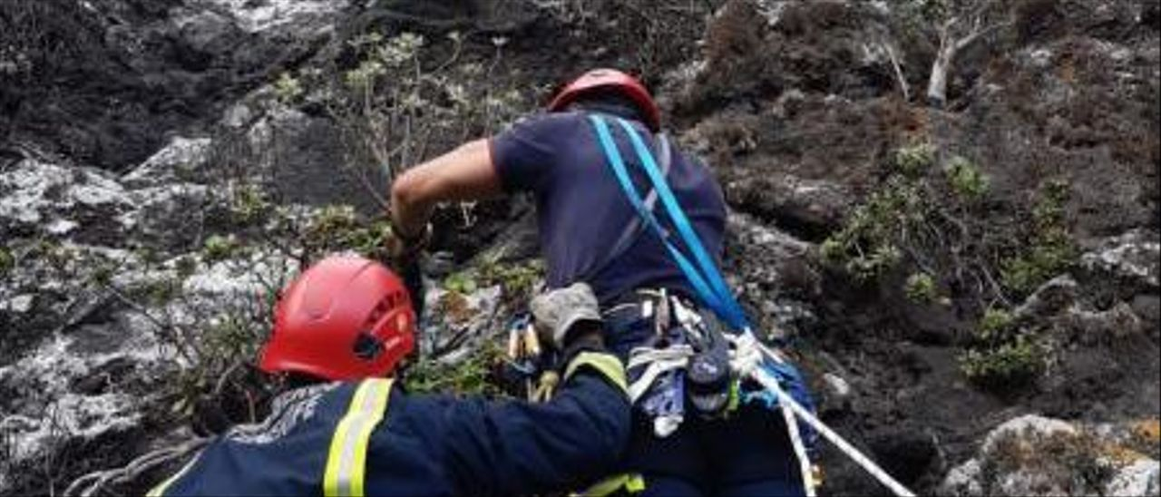 Bomberos de Icod escalan por la ladera para recuperar la vela y la silla.      BOMBEROS