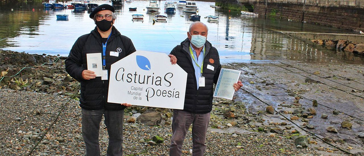 Germán Muiña y Emilio Reiriz, en el puerto de Tapia, con un cartel de promoción del proyecto.   T. Cascudo