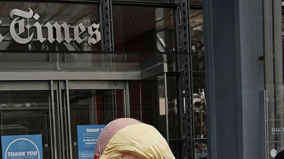 """Un disfrazado de Trump presidiario lee """"The NY Times""""."""