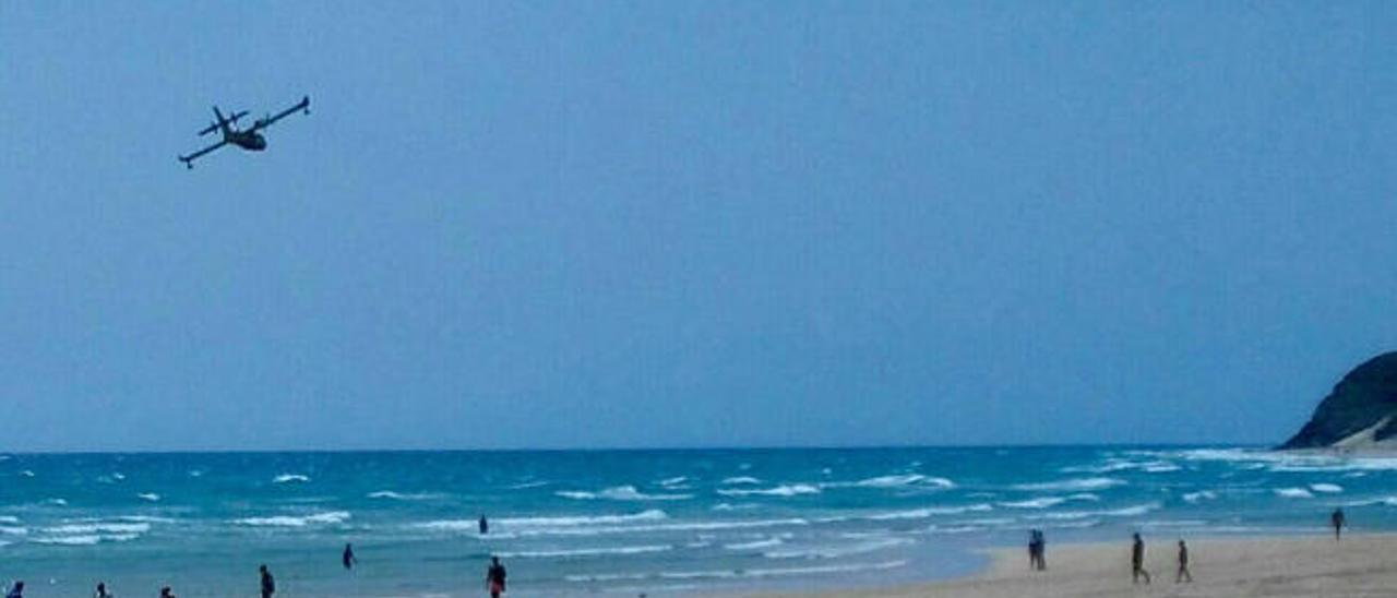 Imagen reciente de un avión sobrevolando las playas de Morro Jable con turistas sobre la arena.