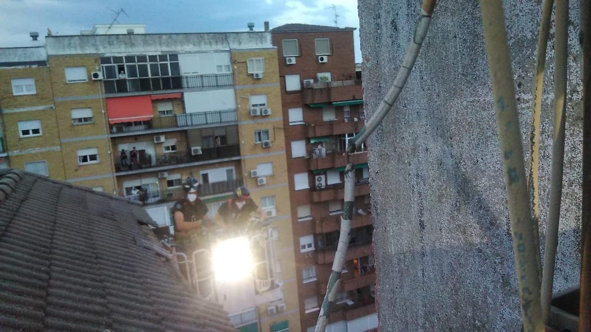 Los bomberos retiran tejas rotas de la cubierta de un bloque de pisos.