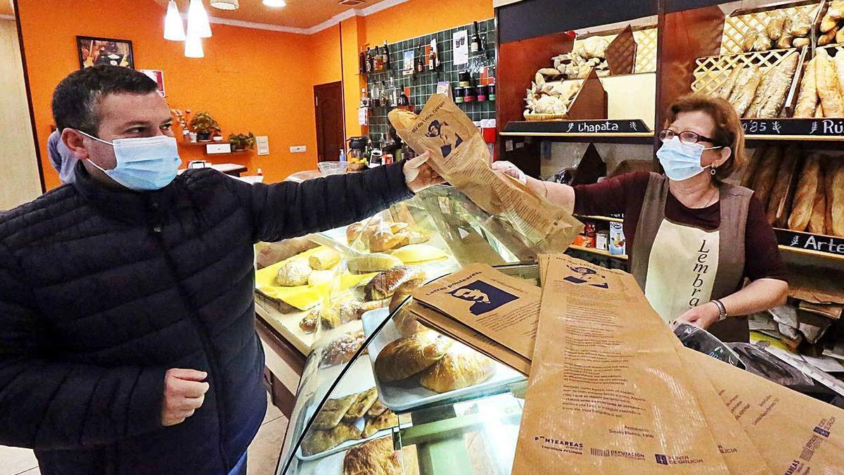 Una panadería de Ponteareas despachando pan con las bolsas conmemorativas.     // D.P.