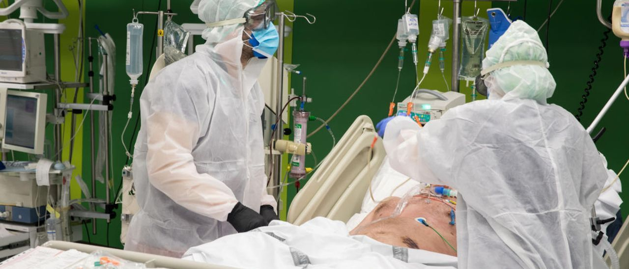 Unos sanitarios atienden a un paciente en la unidad covid del Hospital General de València.