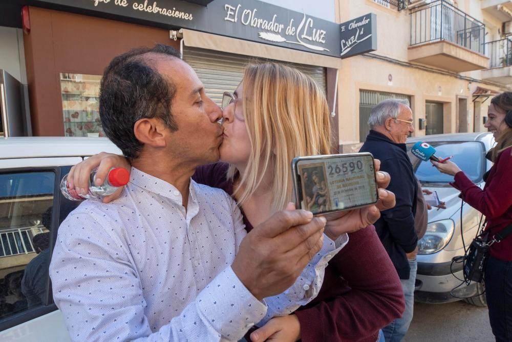 Los agraciados con un número del Gordo de Navidad Yesica Garcia y Alexander Zambrano se besan monstrando el número premiado en Murcia.