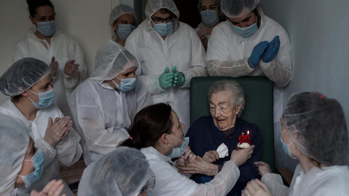 Sanitarios celebran el cumpleaños de una anciana en una residencia.