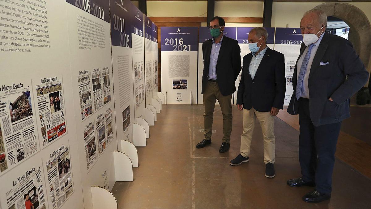 En primer término, Luis Rodríguez-Ovejero, seguido de Antonio Sabino y, a continuación, Íñigo Felgueroso, contemplando algunas de las portadas de la exposición del 30.º aniversario de la edición de LA NUEVA ESPAÑA de Avilés y Comarca.   Ricardo Solís