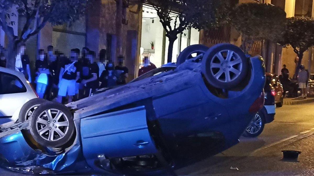 El coche, ruedas arriba en la calle tras el accidente.