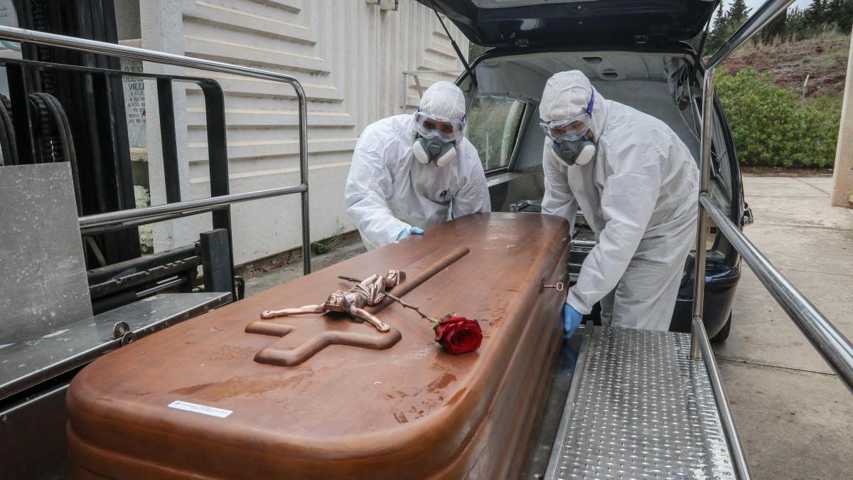 Trabajadores de Parcemasa descargan un ataúd de una víctima de coronavirus, usando un equipo protector completo