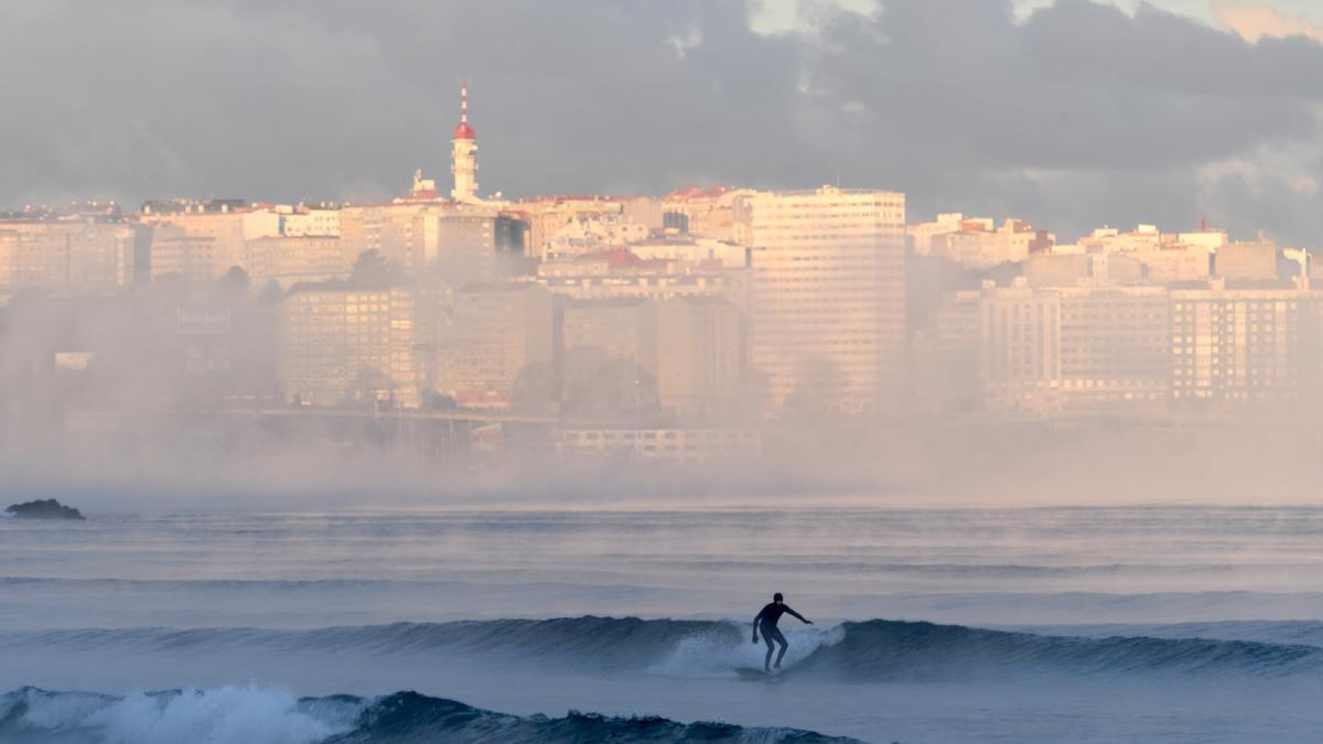 Un joven practicando surf con la ciudad de A Coruña al fondo.