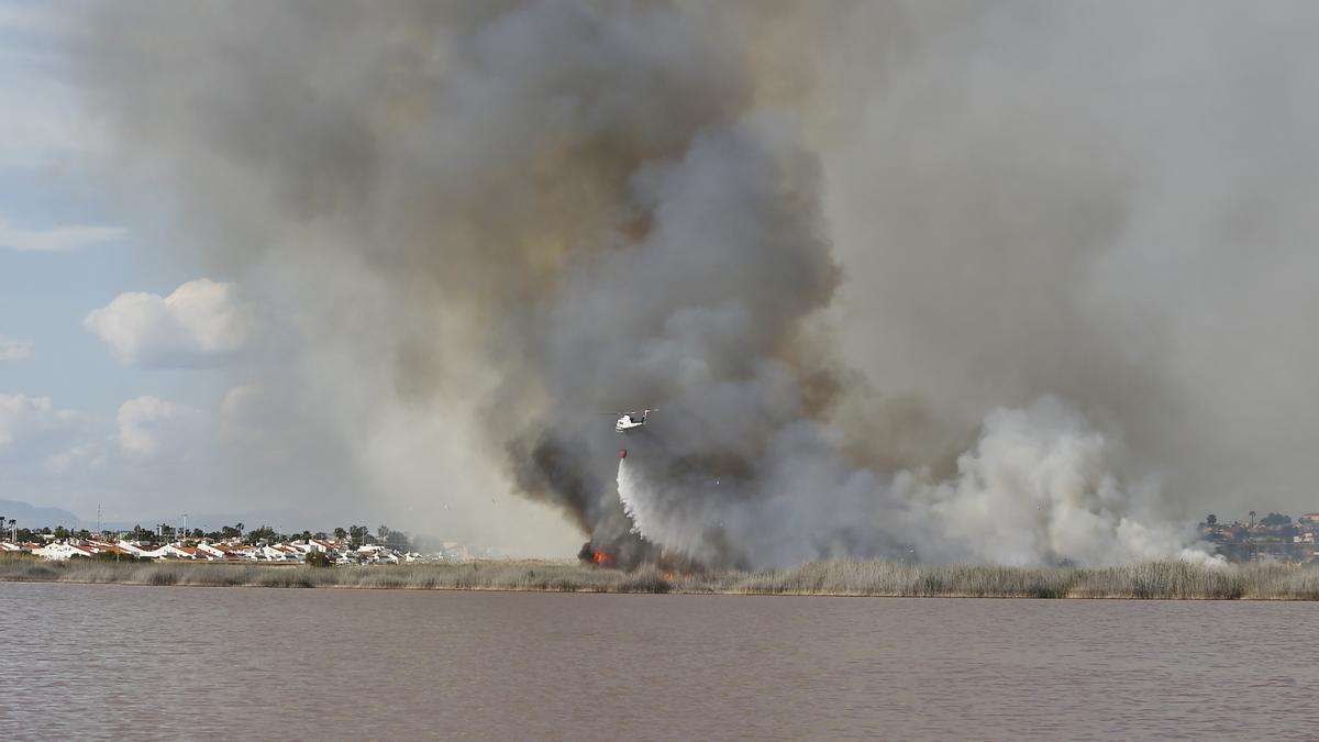 Imagen de la intervención de un helicóptero durante las tareas de extinción del incendio en la laguna rosa junto a Lago Sal