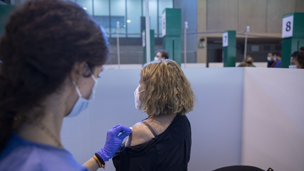 Una sanitaria vacuna a una mujer.