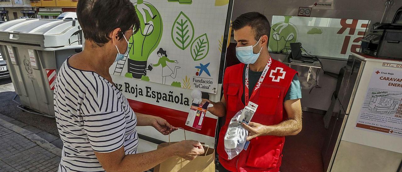 Un trabajador de Cruz Roja entrega un kit de bombillas y regletas a una vecina de Elche durante la salida, ayer, de la caravana de la energía.   