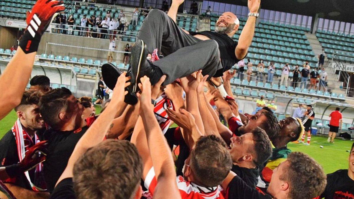Los jugadores mantean a Movilla tras el ascenso del equipo el verano pasado.