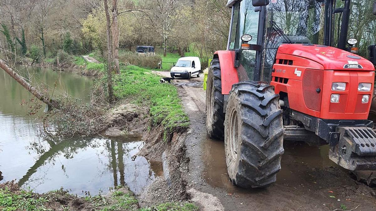 Un tractor y una furgoneta circulan por el camino amenazado por el río Nora a su paso por Quintana. | LNE