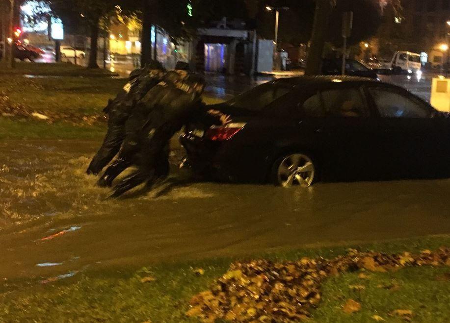 Agentes del Cuerpo Nacional de Policía ayudan a los coches parados por la lluvia en Valencia, anoche.