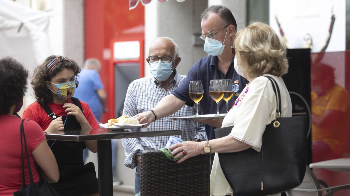 Un hostelero sirve en una terraza en Oviedo el pasado verano. | Miki López