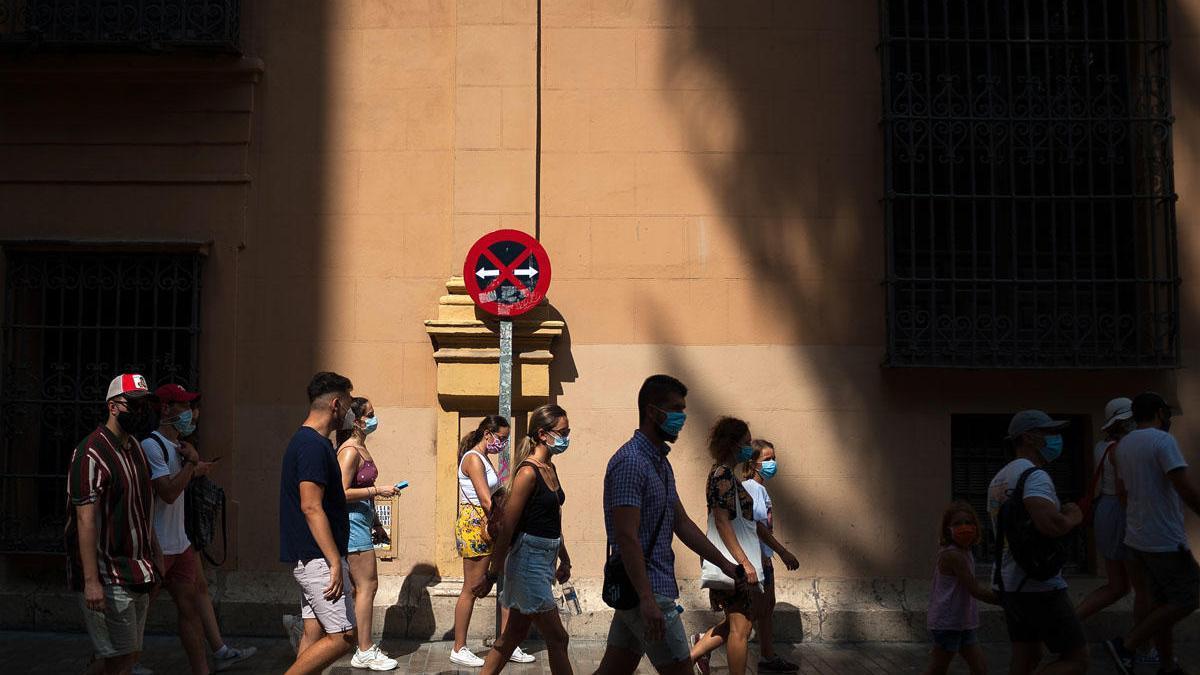 Varias personas caminan por el Centro de Málaga, con sus mascarillas.