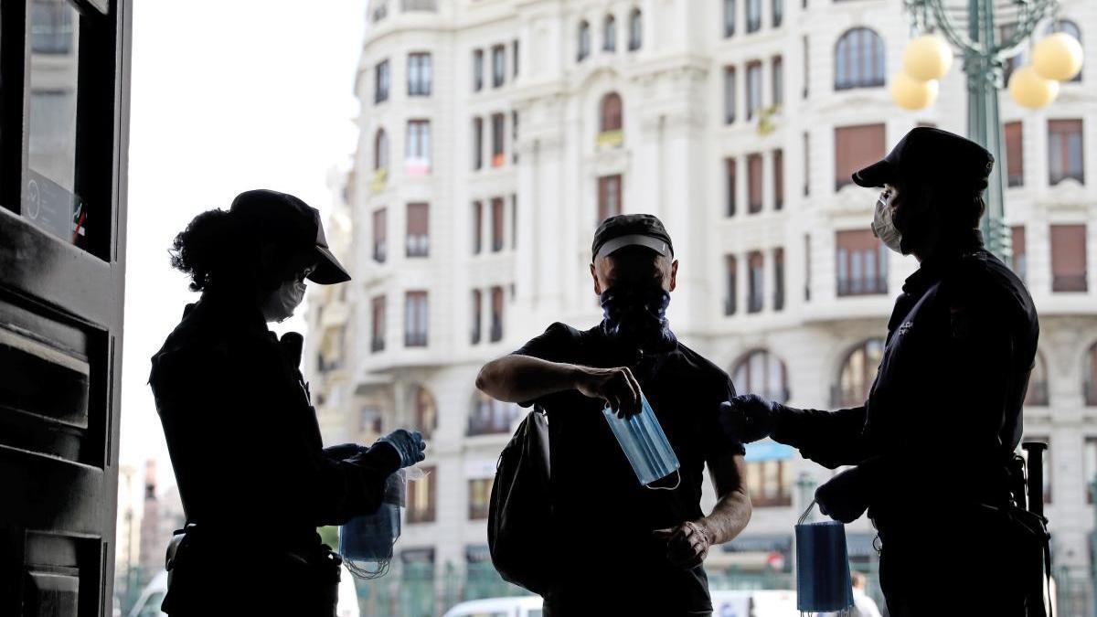 Policías nacionales repartiendo mascarillas en la estación de tren de València