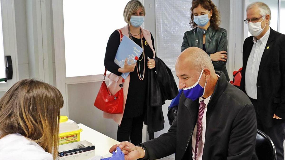 La consellera Vergés observant com el rector de la UdG, Quim Salvi, feia  un test serològic.