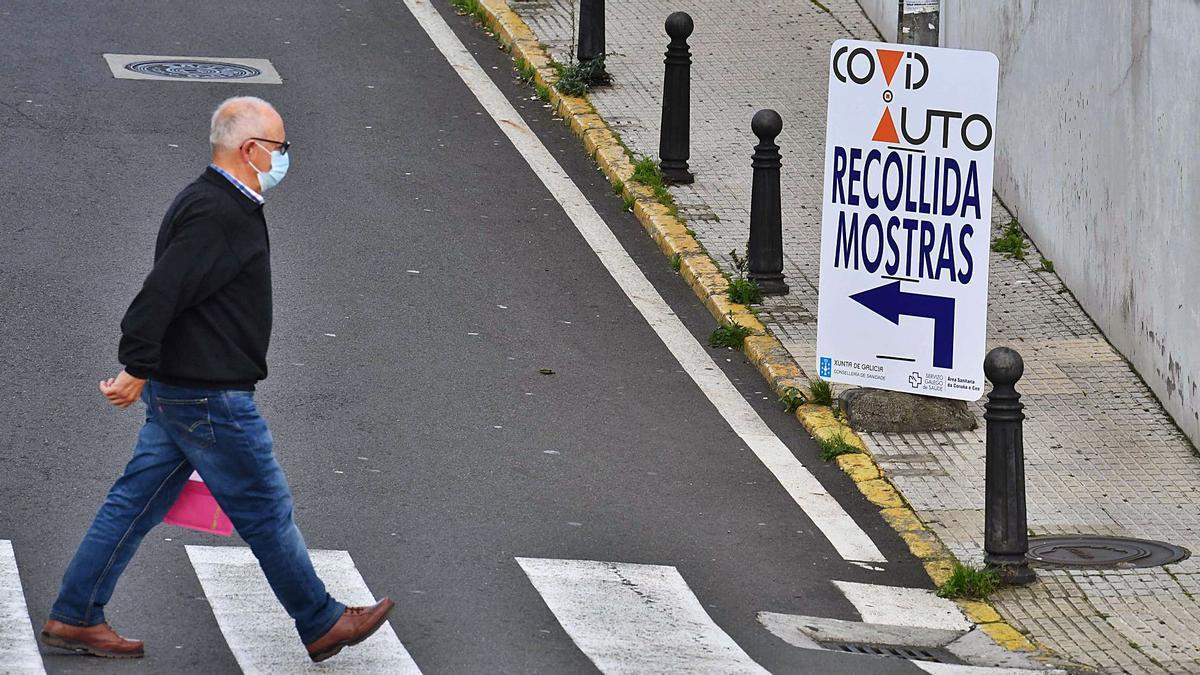 Imagen de archivo de un hombre atravesando un paso de peatones, junto a un cartel que indica la ubicación del 'Covid-auto', en los accesos al Chuac.  | // VÍCTOR ECHAVE