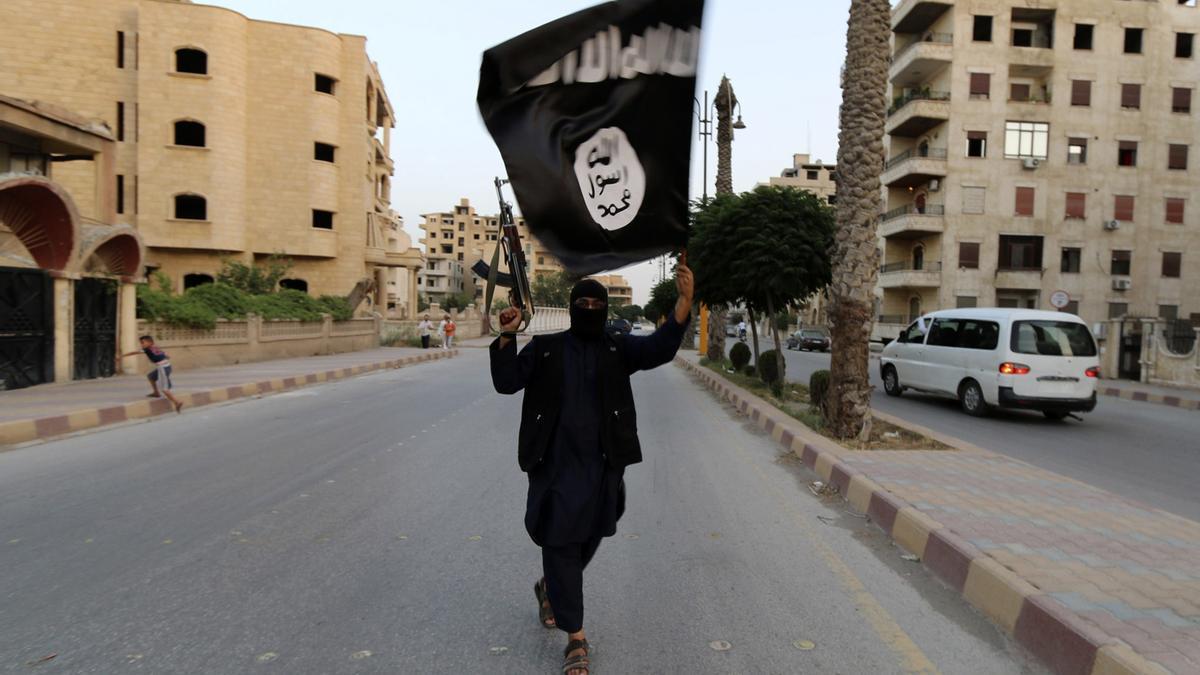 Un hombre con la bandera del denominado Califato Islámico.
