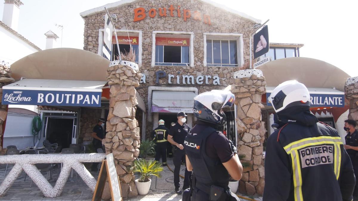 Bomberos y Policía Nacional a las puertas del local donde se ha registrado el incendio.