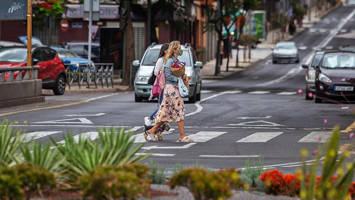 Dos jóvenes con mascarilla transitan por las calles de Santa Cruz de Tenerife.