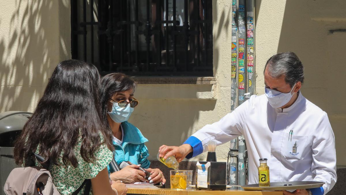 Un camarero sirve un refresco a dos personas en una terraza