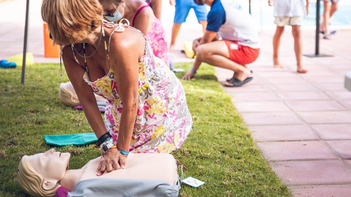 Un grupo de mujeres practican la reanimación cardiopulmnar a los maniquíes siguiendo las instrucciones de personal de Salvasur.