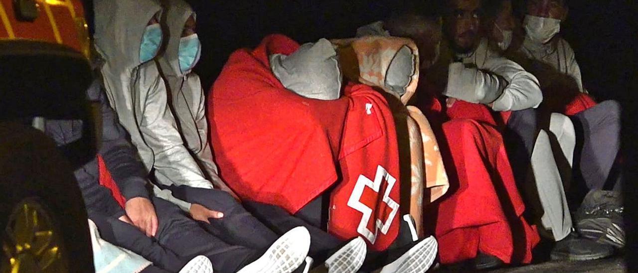 Algunos supervivientes del naufragio de la patera de Órzola se tapan con mantas tras ser rescatados .