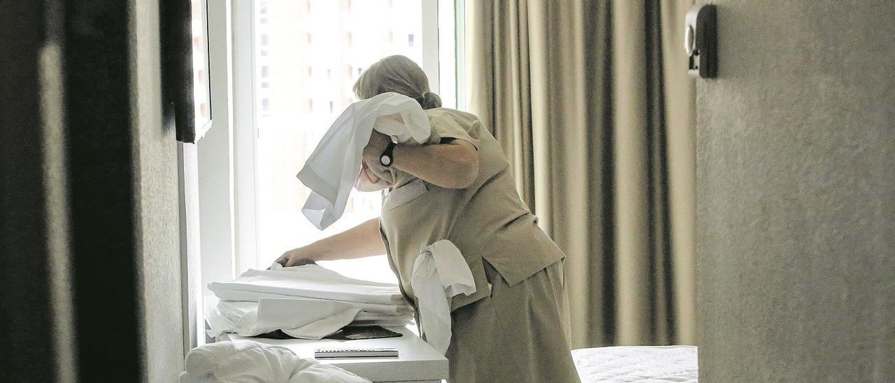 Una «kelly» coge las sábanas para hacer las camas en un hotel de  Benidorm.